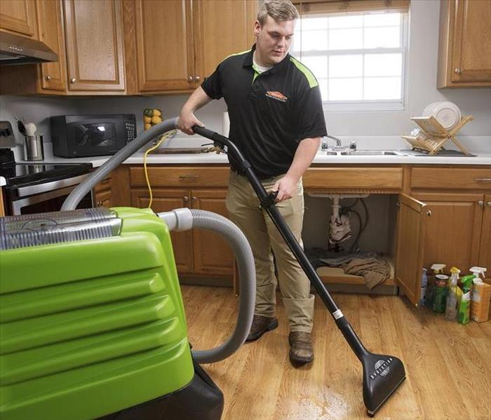 Image is of a SERVPRO technician using a green extraction wand inside a kitchen with a wet floor