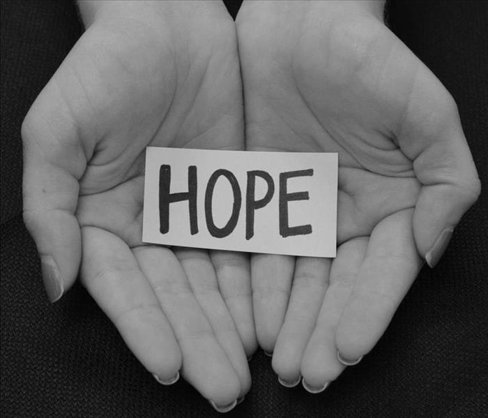 Image shows the palm of hands holding a piece of paper with the word HOPE